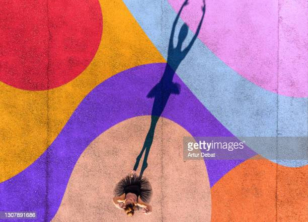 directly above view of ballerina dancing with colorful art in the ground.. - performance stock pictures, royalty-free photos & images