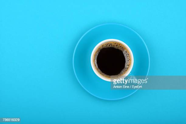 directly above view of black coffee in cup on blue background - platillo fotografías e imágenes de stock