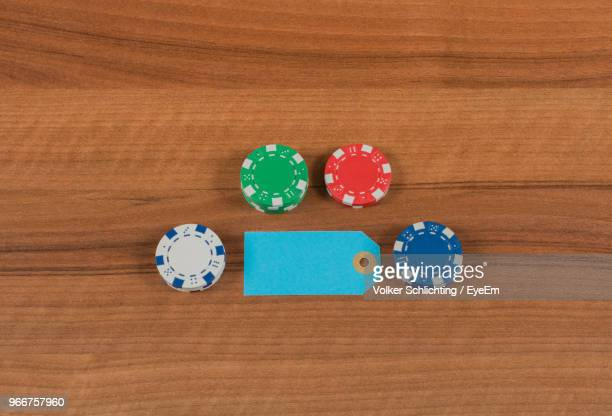 Directly Above View Of Blank Label Amidst Gambling Chips On Wooden Table
