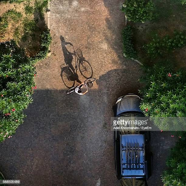 Directly Above View Of Boy Cycling By Car