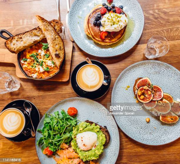 directly above view of breakfast with coffee on wooden table - avocado toast stockfoto's en -beelden
