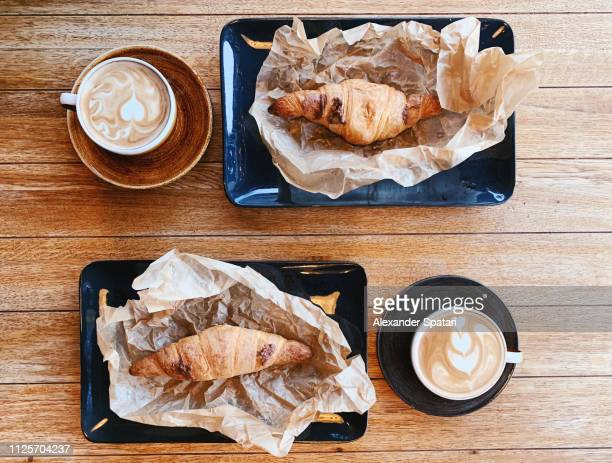 Directly above view of breakfast with croissants and cappuccino on wooden table
