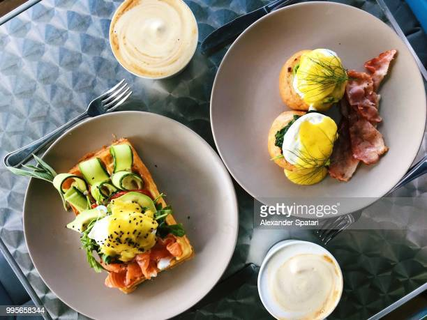 Directly above view of brunch in a cafe with eggs Benedict, waffle, salmon, avocado and coffee