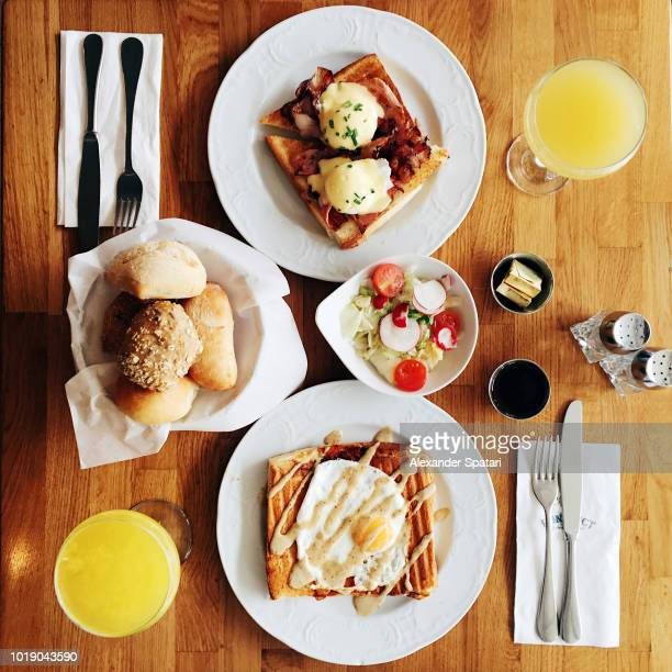 directly above view of brunch with mimosa cocktail, eggs benedict, croque madame and fresh pastry - mimosa stock pictures, royalty-free photos & images