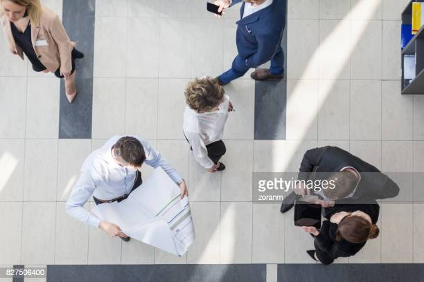 Directly above view of business people in office hallway