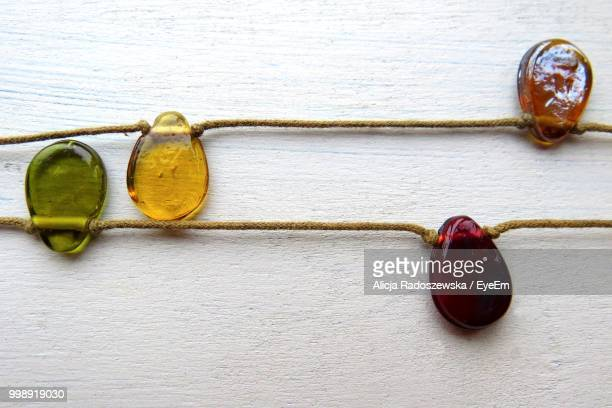 Directly Above View Of Candies On Strings Over White Table
