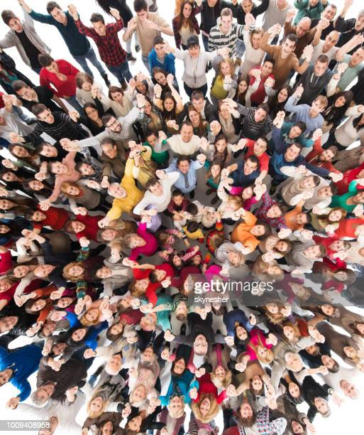 directly above view of cheerful group of people with arms raised looking at camera. - large group of people stock pictures, royalty-free photos & images