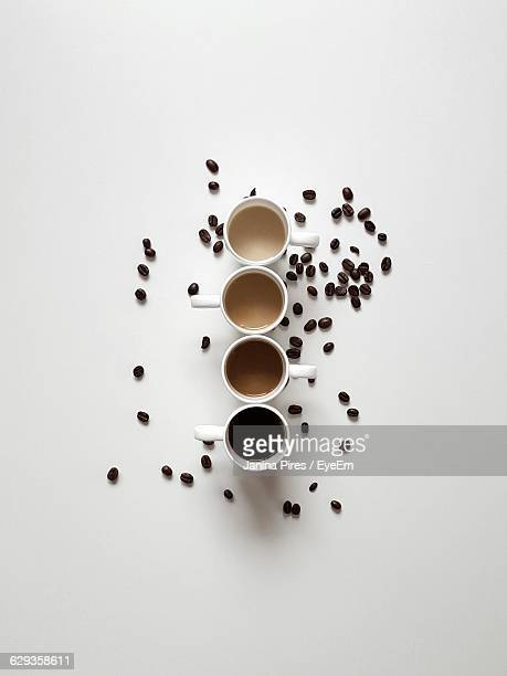 Directly Above View Of Coffee Cups With Scattered Beans On White Background