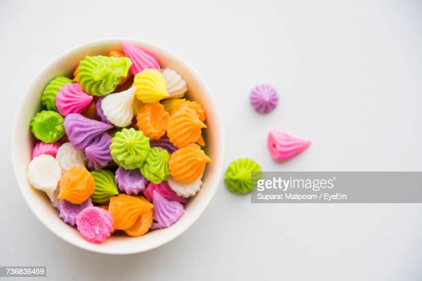 directly above view of colorful candies in bowl on white background - bowl of candy stock photos and pictures