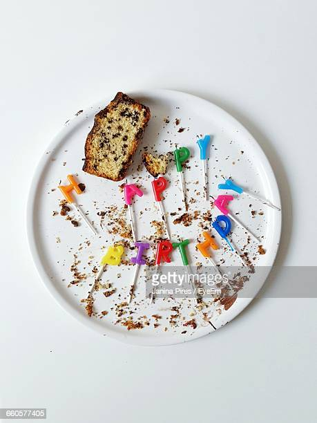 Directly Above View Of Colorful Candles With Cake Slice In Plate On White Background