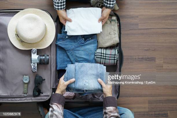 directly above view of couple packing suitcase on hardwood floor - pack fotografías e imágenes de stock