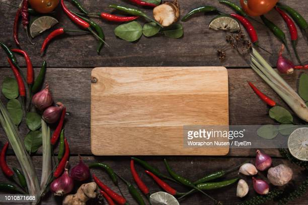 directly above view of cutting board amidst vegetables on table - pepper vegetable stock pictures, royalty-free photos & images