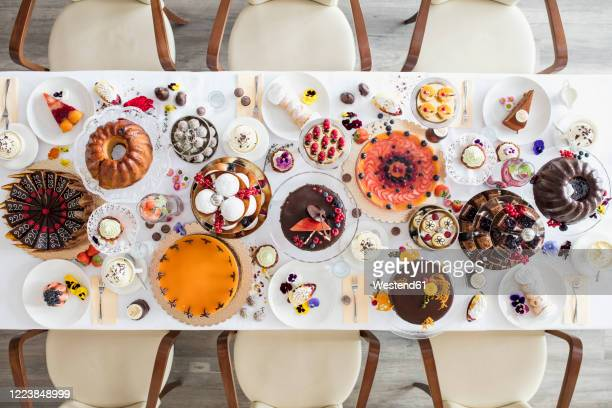 directly above view of dining table filled with all kinds of snacks and desserts - dessert photos et images de collection
