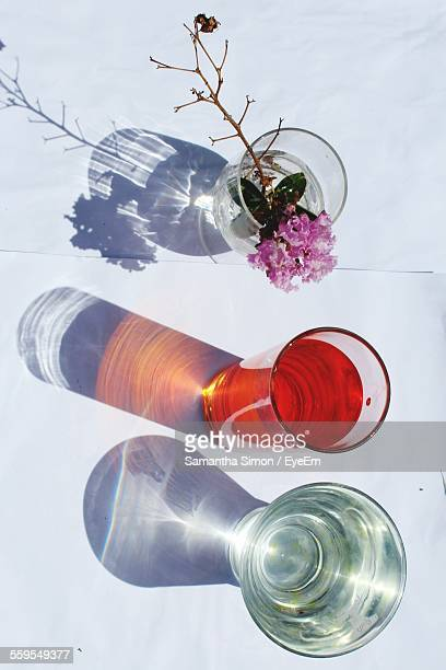 Directly Above View Of Drinking Glasses With Water Drink And Flower Against White Surface