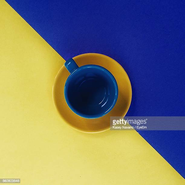 Directly Above View Of Empty Coffee Cup And Saucer On Blue Yellow Table