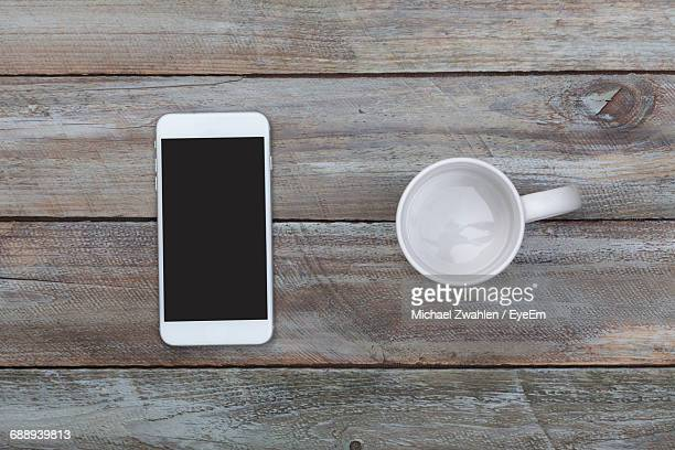 Directly Above View Of Empty Coffee Mug And Mobile Phone On Table