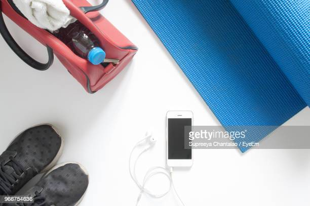 Directly Above View Of Exercise Mat By Smart Phone With Purse And Sports Shoe