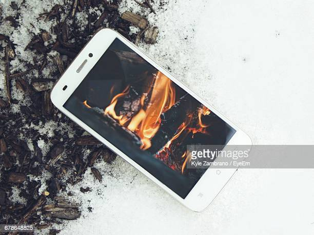 Directly Above View Of Fire Display On Mobile Phone Over Ash And Snow