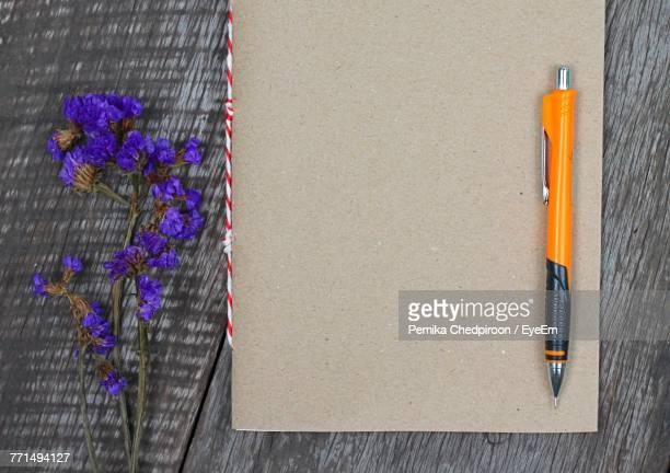 Directly Above View Of Flowers And Diary With Pen On Table