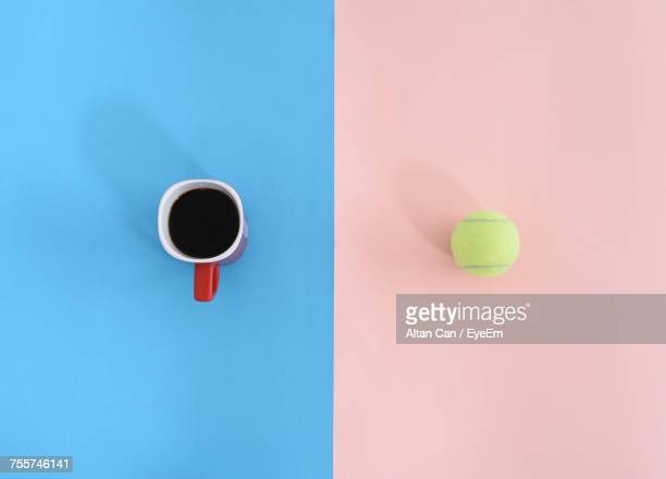 Directly Above View Of Fresh Black Coffee In Cup And Tennis Ball On Table