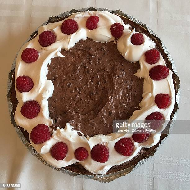 Directly Above View Of Fresh Chocolate Pie With Raspberry Fruits On Table