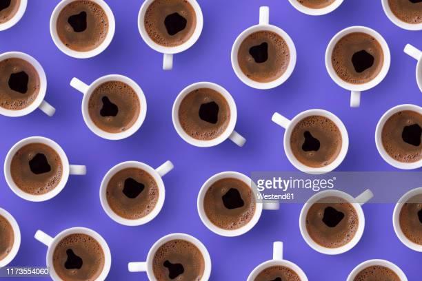 directly above view of fresh coffee in cups over purple background - tazza da caffè foto e immagini stock