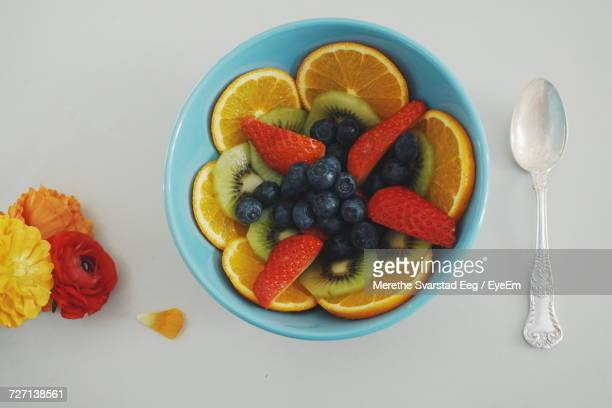 Directly Above View Of Fresh Fruits In Bowl By Flowers And Silver Spoon On White Background