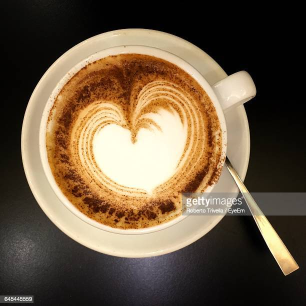 Directly Above View Of Fresh Heart Shape Froth On Coffee Against Black Background
