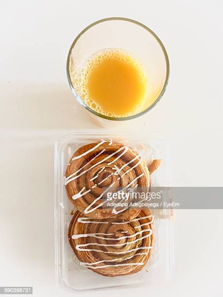 Directly Above View Of Fresh Pretzel In Plastic Container With Orange Juice On White Background