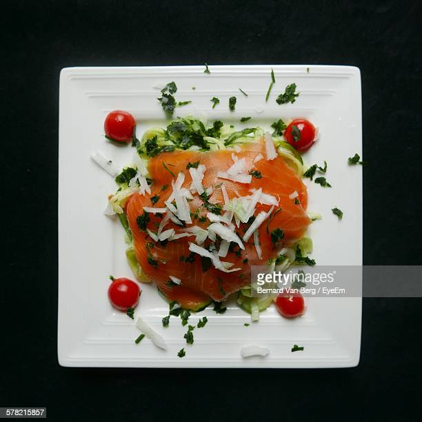 Directly Above View Of Fresh Sliced Zucchini Salad With Trout Meat In Plate Against Black Background