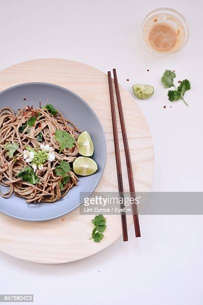 Directly Above View Of Fresh Soba Noodles Served In Bowl With Chopsticks On White Background