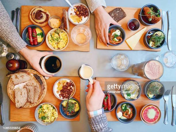 directly above view of friends eating brunch at the restaurant - danish food stock pictures, royalty-free photos & images