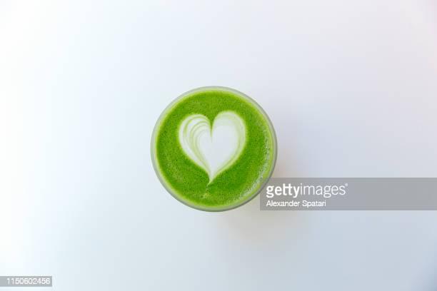 directly above view of green matcha tea latte with heart shaped latte art - hoja te verde fotografías e imágenes de stock