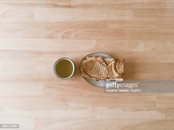 directly above view of green tea and taiyaki on table - 和菓子 ストックフォトと画像