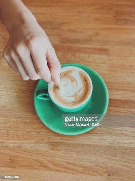 Directly Above View Of Hand Holding Coffee Cup On Table