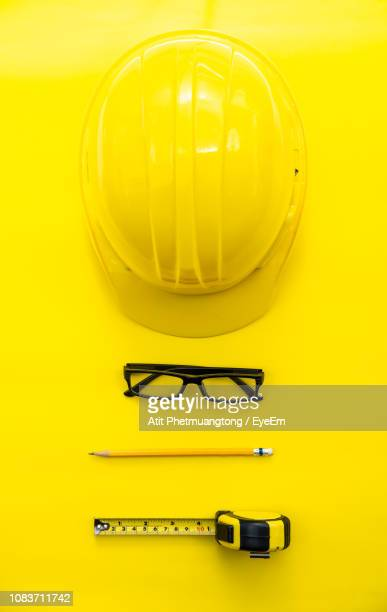 directly above view of hardhat by eyeglasses and pencil with tape measure on yellow background - still life not people stock photos and pictures