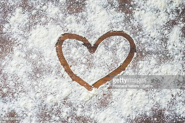 Directly Above View Of Heart Shape On Flour Over Table