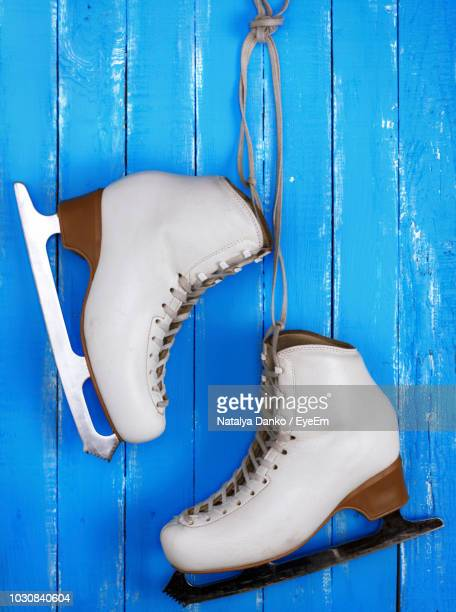 directly above view of ice skates on blue wooden table - ice skate stock pictures, royalty-free photos & images