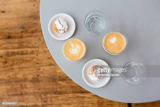 Directly above view of latte, profiteroles and glasses of water on the table in coffee shop
