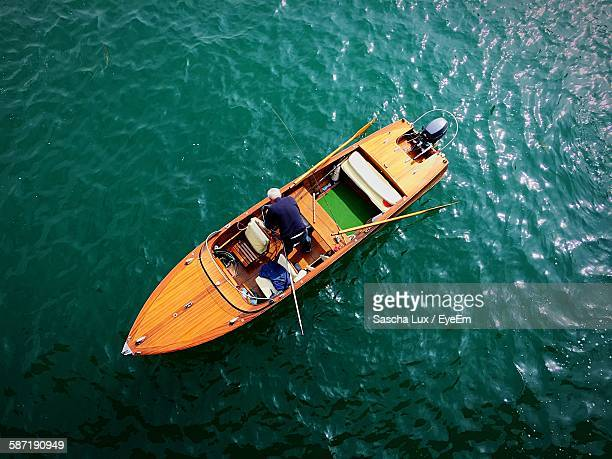 Directly Above View Of Man On Motorboat Over Lake