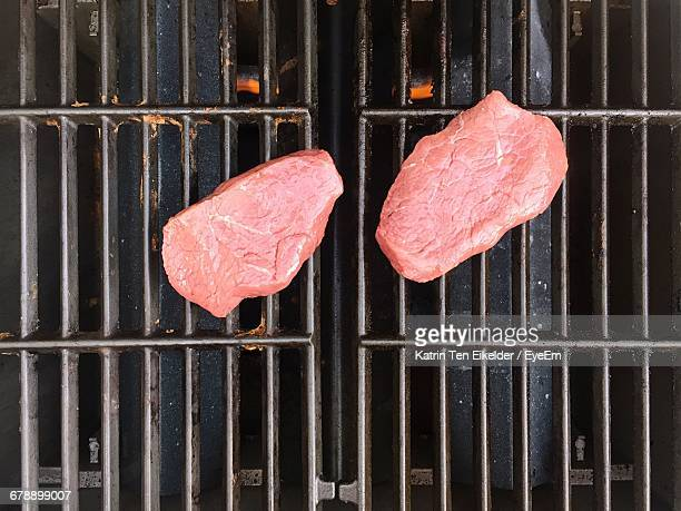 directly above view of meat on barbecue grill - metal grate stock photos and pictures