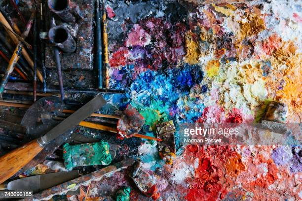 Directly above view of messy paints and tubes with equipment