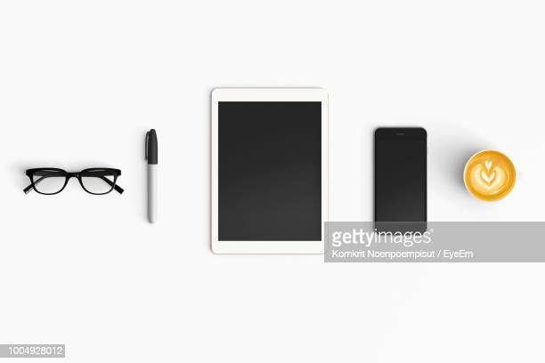 directly above view of mobile phone and digital tablet over white background - pc ultramobile foto e immagini stock
