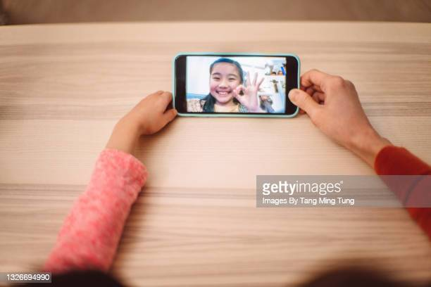directly above view of mom & daughter having video call with family at home - internet stock pictures, royalty-free photos & images