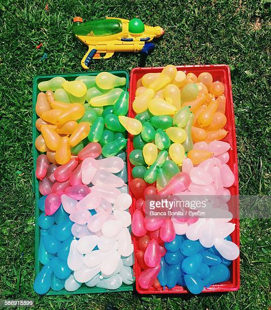 Directly Above View Of Multi Colored Water Bombs In Container By Squirt Gun On Field
