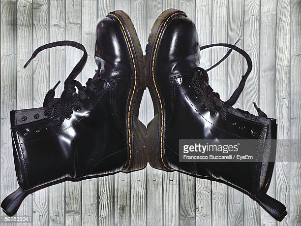 directly above view of new black boots on wood - black boot stock pictures, royalty-free photos & images