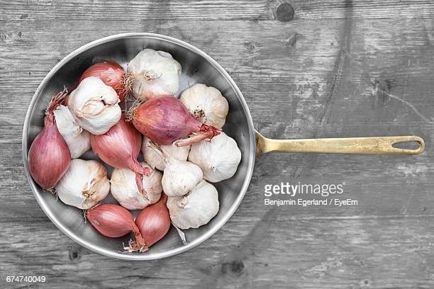 Directly Above View Of Onions And Garlic Cloves In Cooking Utensil On Table