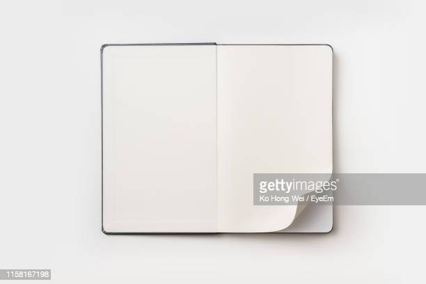 directly above view of open book on white background - ページ ストックフォトと画像