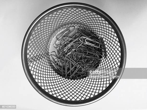 Directly Above View Of Paperclips In Metallic Bin On White Background