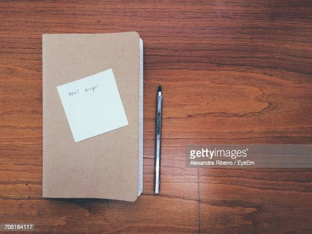 Directly Above View Of Pen By Message On Diary Over Table